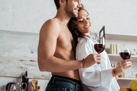 low angle view of happy muscular man holding wine glass near attractive and happy girl at home