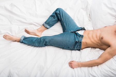 cropped view of muscular man lying on bed in blue jeans