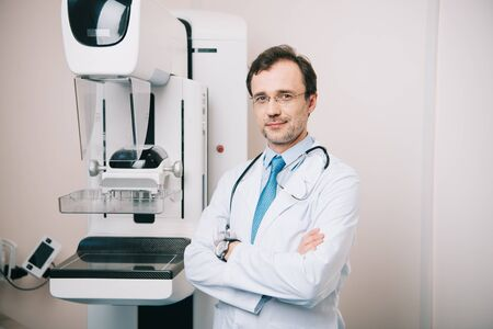 smiling doctor standing with crossed arms near x-ray machine and looking at camera