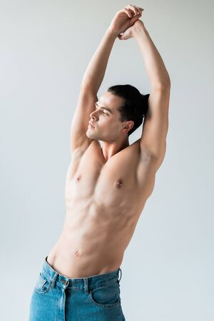 handsome shirtless man standing with hands above head on white
