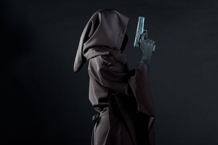Side view of woman in death costume holding gun isolated on black background