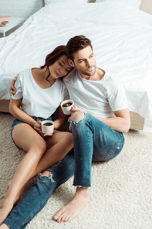 overhead view of handsome man and girl sitting on carpet and holding cups
