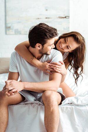 happy young woman hugging handsome boyfriend in bedroom