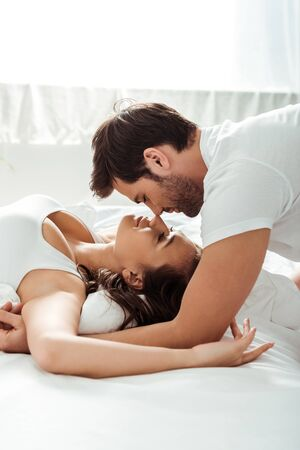 happy man with closed eyes near girlfriend lying on bed