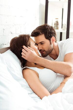 handsome man touching hair of attractive woman in bedroom Reklamní fotografie