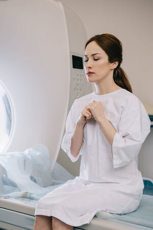 Attractive woman praying with closed eyes while sitting on mri scanner bed in hospital