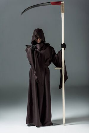 Full length view of woman in death costume holding scythe and pointing with finger on grey background