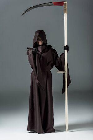 Ganzkörperansicht einer Frau im Todeskostüm, die Sense hält und mit dem Finger auf grauem Hintergrund zeigt Standard-Bild