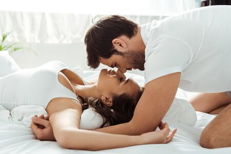 happy young woman lying on bed and looking at boyfriend Reklamní fotografie