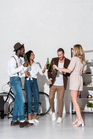 happy stylish multicultural friends holding bottles of beer at home Reklamní fotografie