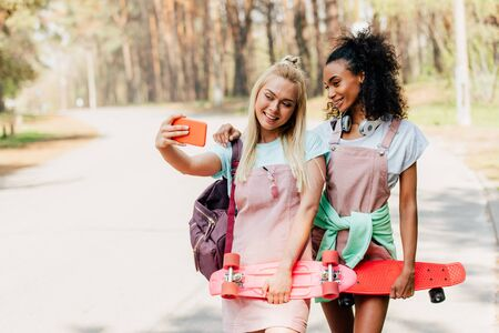 two smiling multiethnic friends holding penny boards and taking selfie on road