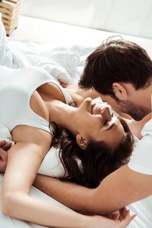 boyfriend near happy girlfriend with closed eyes lying on bed
