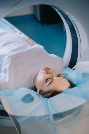 Pretty Woman acostada con los ojos cerrados en la cama del escáner CT durante el diagnóstico Foto de archivo