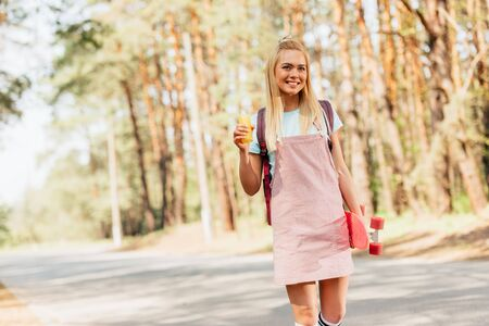 blonde smiling girl with skateboard holding bottle of orange juice on road