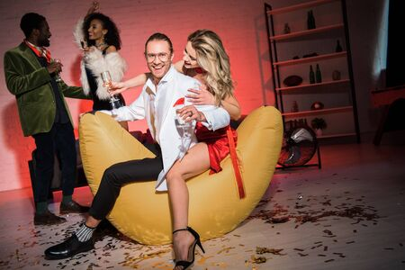 selective focus of happy girl in red dress sitting with man on bean bag chair near friends