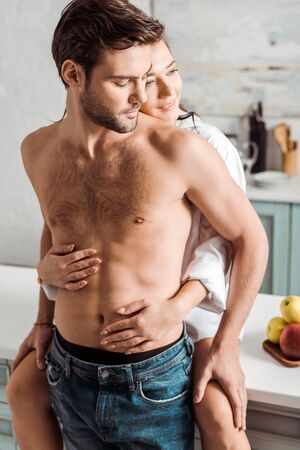 cheerful and pretty girl embracing handsome muscular man in kitchen Reklamní fotografie