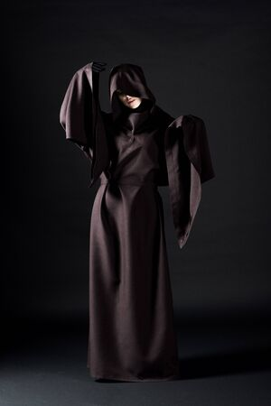 Full length view of woman in death costume on black background