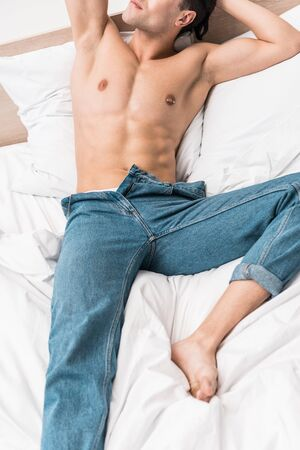 cropped view of shirtless man in jeans lying on bed at home