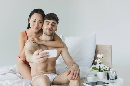 happy interracial couple sitting on white bedding in underwear and taking selfie with smartphone