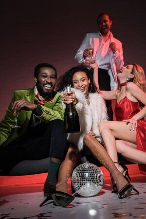 low angle view of african american man holding champagne glass while sitting with multicultural friends
