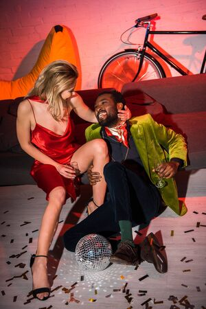 young blonde woman in red dress sitting with african american man in night club Reklamní fotografie