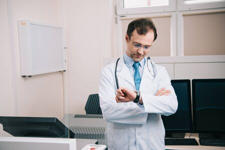 Handsome doctor in white coat and glasses checking time at watch Foto de archivo