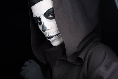 Woman with skull makeup looking at camera isolated on black background