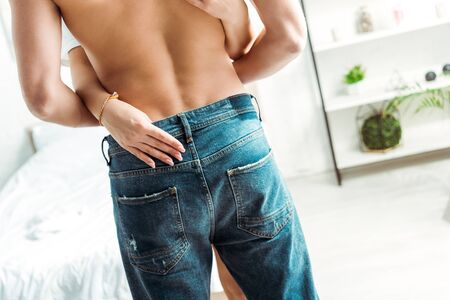 back view of muscular man standing in jeans near girlfriend in bedroom