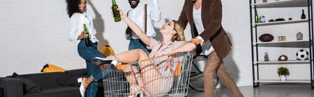 panoramic shot of happy stylish girl riding in shopping cart near multicultural friends holding bottles of beer
