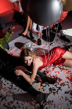 overhead view of happy girl holding balloons while lying on floor near friends