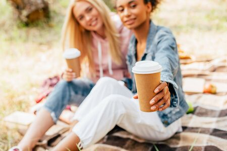 cropped view of two multiethnic friends sitting on plaid blanket and holding paper cups of coffee