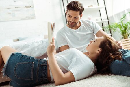 low angle view of handsome man looking at book in hands of girl lying on carpet in bedroom