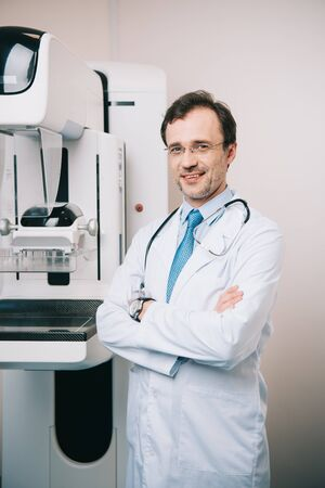 smiling radiologist standing near x-ray machine with crossed arms and looking at camera