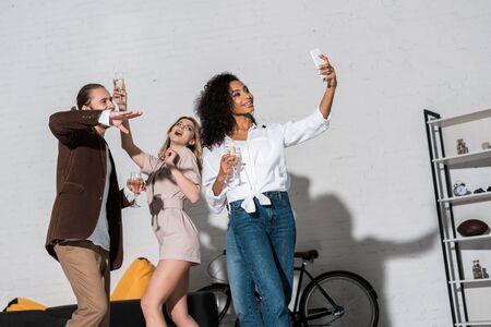 low angle view of attractive african american girl taking selfie with friends holding champagne glasses Reklamní fotografie