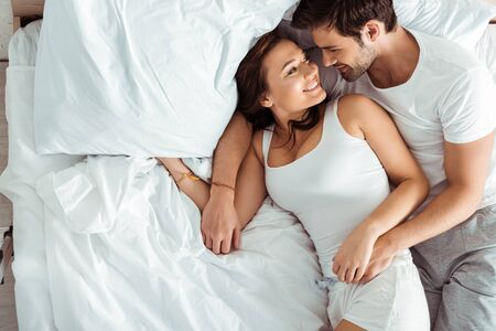 top view of cheerful man looking at happy woman while holding hands and lying on bed