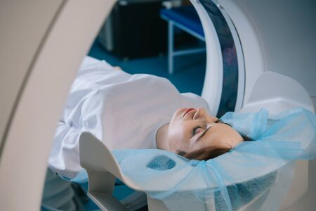 Young woman lying on ct scanner bed during tomography diagnostics in hospital Zdjęcie Seryjne
