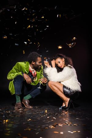 cheerful african american man and beautiful african american woman holding champagne glasses while sitting near falling confetti on black Reklamní fotografie