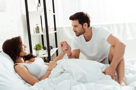 handsome man looking at attractive woman lying in bed and holding hands Reklamní fotografie