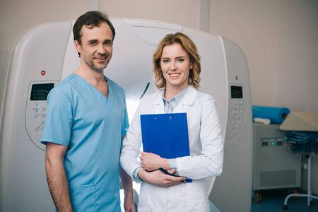 Smiling doctors looking at camera while standing near computed tomography scanner Zdjęcie Seryjne