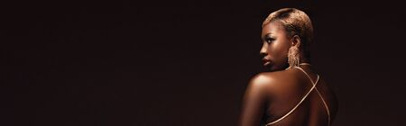 Glamorous trendy African American woman with short hair isolated on brown background Stock Photo