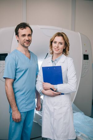 Beautiful radiologist holding clipboard while standing near assistant and looking at camera