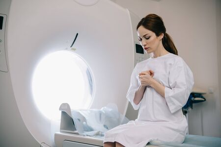 Beautiful woman praying with closed eyes while sitting on mri scanner bed in hospital Zdjęcie Seryjne - 125221021