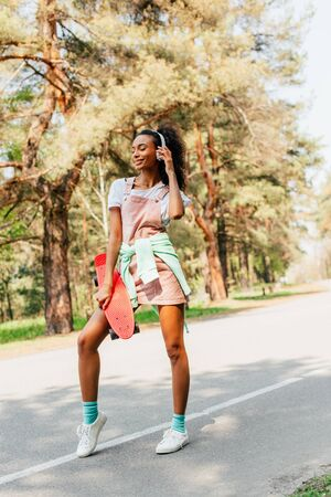Full length view of African American girl in headphones standing on road and holding penny board