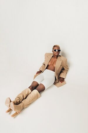 Fashionable African American girl posing in trendy sunglasses and beige jacket on grey background