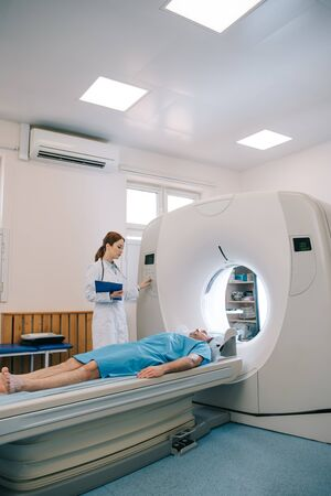 Radiologist in white coat operating ct scanner while patient lying on ct scanner bed