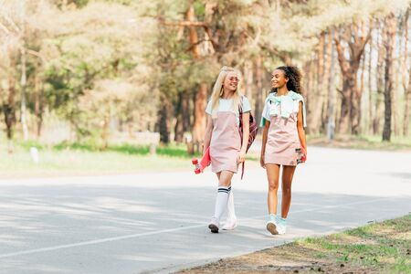 Full length view of smiling multicultural friends with penny boards walking on road