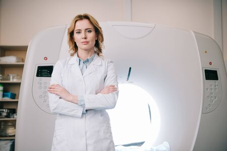 Attractive confident radiologist standing near mri machine with crossed arms and looking at camera