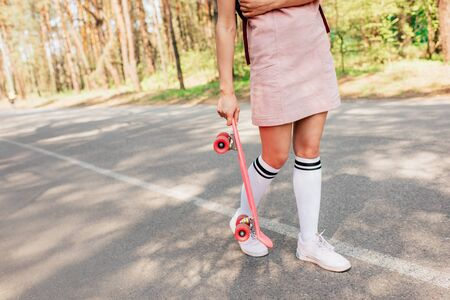 Cropped view of girl in knee socks holding penny board on road