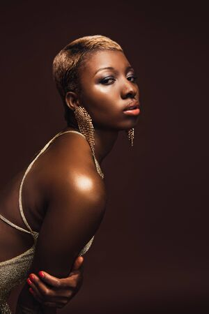 Fashion Shoot with African American woman with short hair isolated on brown background