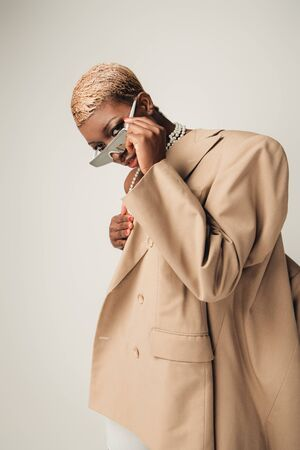 Stylish African American girl with short hair posing in sunglasses and beige jacket isolated on grey background
